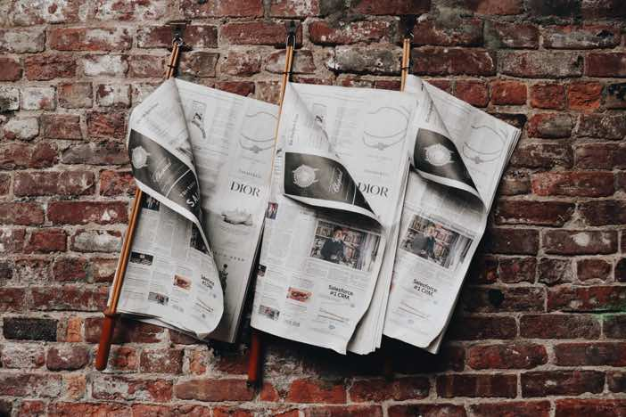 Newspapers hanging up on a brick wall